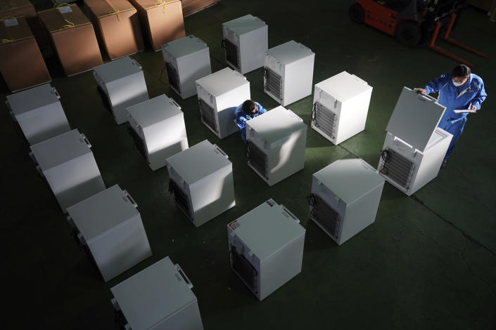 Brand-new ultralow-temperature freezers are seen at a warehouse at Kanou Reiki, a freezer supplier, Friday, Jan. 22, 2021 in Sagamihara, west of Tokyo. Some of COVID-19 vaccine must be kept at the ultra-cold temperature of around -70 degrees Celsius (-94 degrees Fahrenheit). Japan is accelerating preparations for COVID-19 vaccinations in hopes of starting them in late February, but uncertainty is growing as the country faces vaccine-shy public, slow approval process and bureaucratic roadblocks, casting a doubt if Tokyo Olympic this summer is possible. (AP Photo/Eugene Hoshiko)