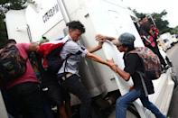Honduran migrants, part of a caravan trying to reach the U.S., climb on a truck during a new leg of her travel in Zacapa, Guatemala October 17, 2018. REUTERS/Edgard Garrido