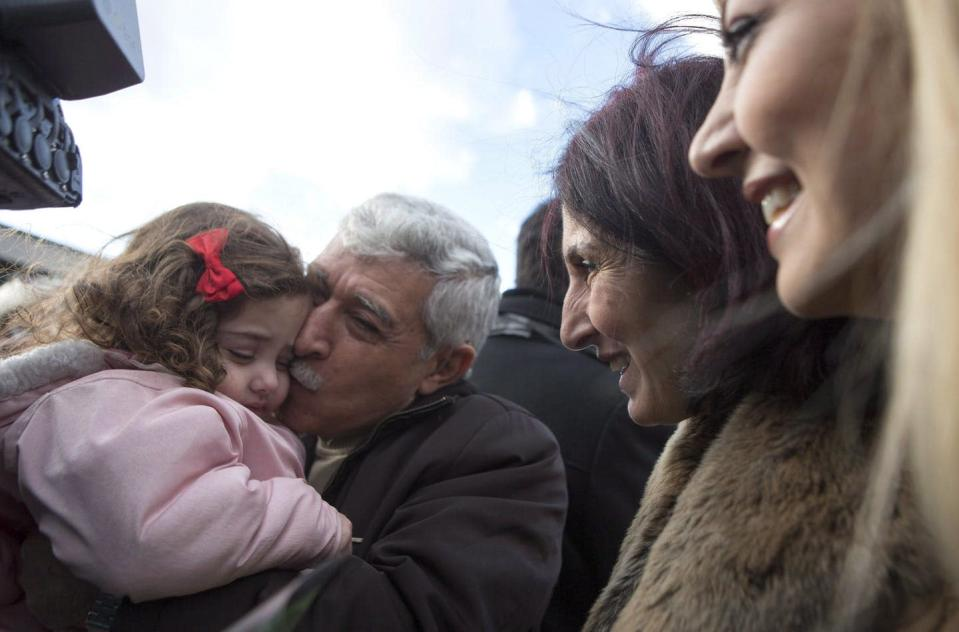 A Syrian-Canadian man hugs and kisses his newly arrived grand-daughter