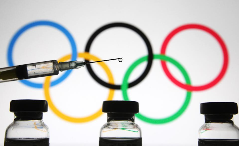 UKRAINE - 2021/01/01: In this photo illustration a medical syringe and vials are seen in front of the Olympic Games rings. #The World Health Organization (WHO) on 31 December 2020 lists Pfizer/BioNTech vaccine for emergency use, as media reported. (Photo Illustration by Pavlo Gonchar/SOPA Images/LightRocket via Getty Images)