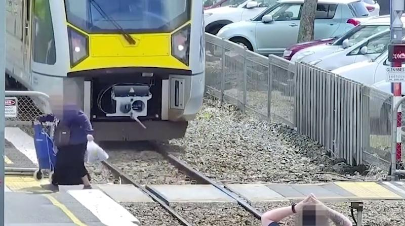 An elderly woman with a trolley crosses in the path on an incoming train in New Zealand.