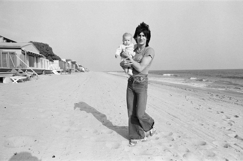<p>Ronnie Wood of the Rolling Stones carries his baby Jesse James Wood on the beach of their Malibu home in 1977.</p>