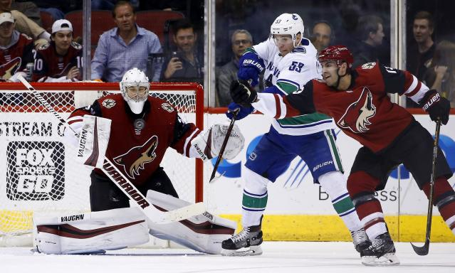 Arizona Coyotes goaltender Darcy Kuemper, left, makes a save as Vancouver Canucks center Bo Horvat (53) and Coyotes center Freddie Hamilton, right, battle in front of the net during the second period of an NHL hockey team Sunday, March 11, 2018, in Glendale, Ariz. (AP Photo/Ross D. Franklin)