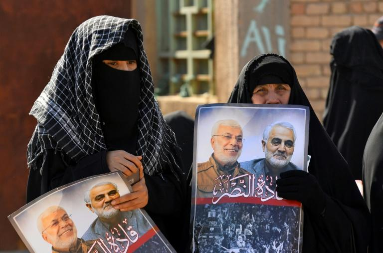 Iraqi women hold portraits of Iran's late top general Qasem Soleimani and Iraqi paramilitary commander Abu Mahdi al-Muhandis, killed in a US drone strike near Baghdad in January 2020