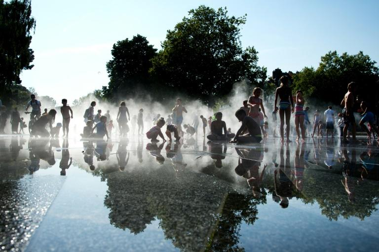 Children cool off in a mirrored fountain during a heat wave (AFP Photo/Jean-Sebastien Evard)