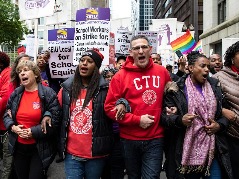 Chicago Teachers Union Vice President Stacy Davis Gates, center, left, and CTU President Jesse Sharkey, center, right, lead thousands of striking union members on a march through the Loop, Thursday, Oct. 17, 2019, in Chicago. Striking teachers went on strike after their union and city officials failed to reach a contract deal in the nation's third-largest school district. (Ashlee Rezin Garcia/Chicago Sun-Times via AP)