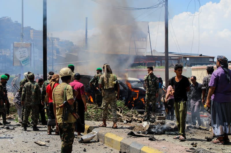 Policemen and people gather at the scene of a blast in Aden