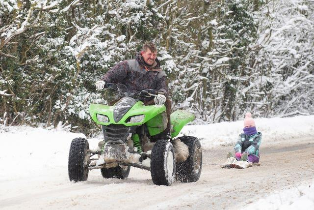 Richard Squirrell uses a quad bike to give his granddaughter Florence a ride in the snow in Wattisham in Suffolk