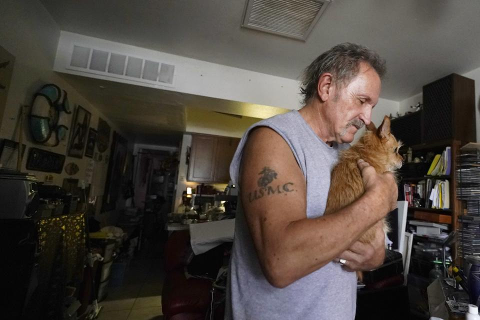 Rental resident Paul Wunder holds his dog Missy as he speaks about his eviction notice after meeting with Pima County Constable Kristen Randall Friday, Sept. 24, 2021, in Tucson, Ariz. Long delayed evictions are rolling out more than a month after the end of a federal moratorium that had protected tenants, including some who hadn't paid rent for many months during the coronavirus pandemic. (AP Photo/Ross D. Franklin)