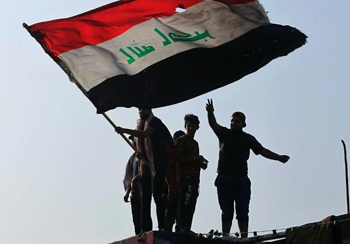 Iraqi demonstrators wave a flag as they gather in Tahrir Square in the centre of the capital Baghdad to mark the first anniversary of a movement demanding the ouster of the entire ruling class accused of corruption