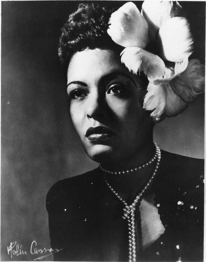 <p>Billie Holiday poses for a studio portrait in a long-sleeved sequin dress, accessorized with a long strand of pearls and flowers in her hair. </p>