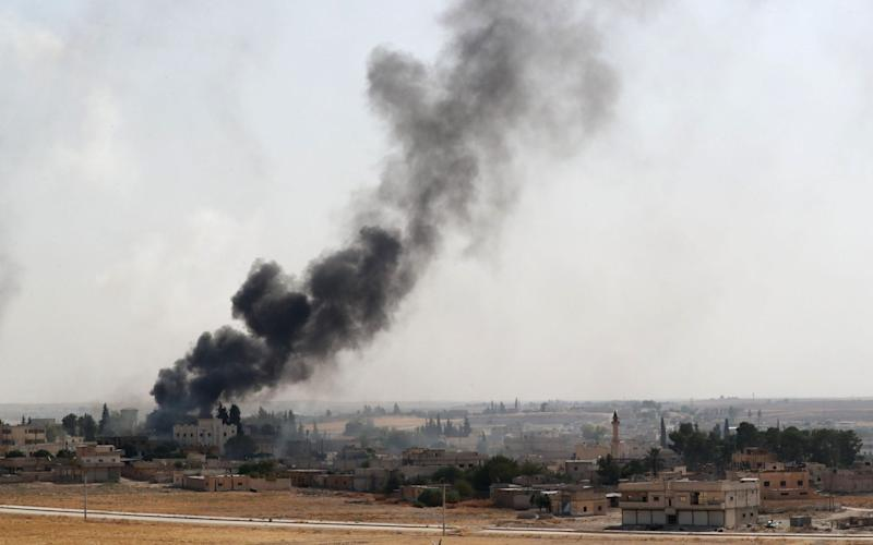Smoke rises from a Turkish bombardment in northeast Syria on Sunday, seen from the Turkish side of the border - REX