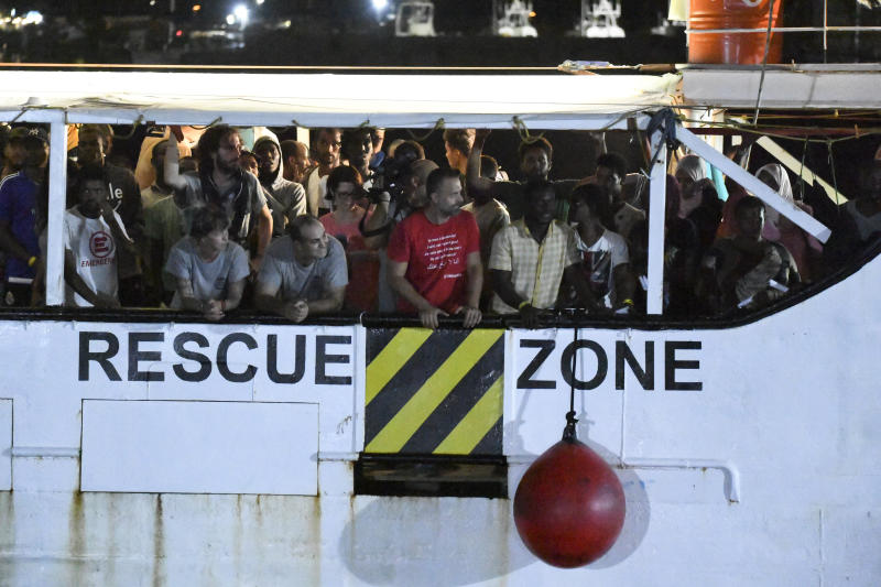 The Open Arms rescue ship arrives on the Sicilian island of Lampedusa, southern Italy, Tuesday, Aug. 20, 2019. Italian prosecutor Luigi Patronaggio has ordered the seizure of a migrant rescue ship and the immediate evacuation of more than 80 migrants remaining on board, capping dramatic developments that saw 15 migrants jump into the sea in a desperate bid to reach land and the Spanish government dispatch a Naval ship on a long journey to resolve the escalating crisis. (AP Photo/Salvatore Cavalli)