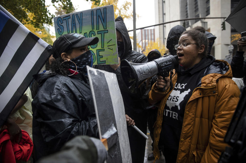 Back the Blue police supporters, left, stand next to Black Lives Matter protesters calling for defunding the police, Thursday, Nov. 5, 2020, in Portland, Ore. (AP Photo/Paula Bronstein)