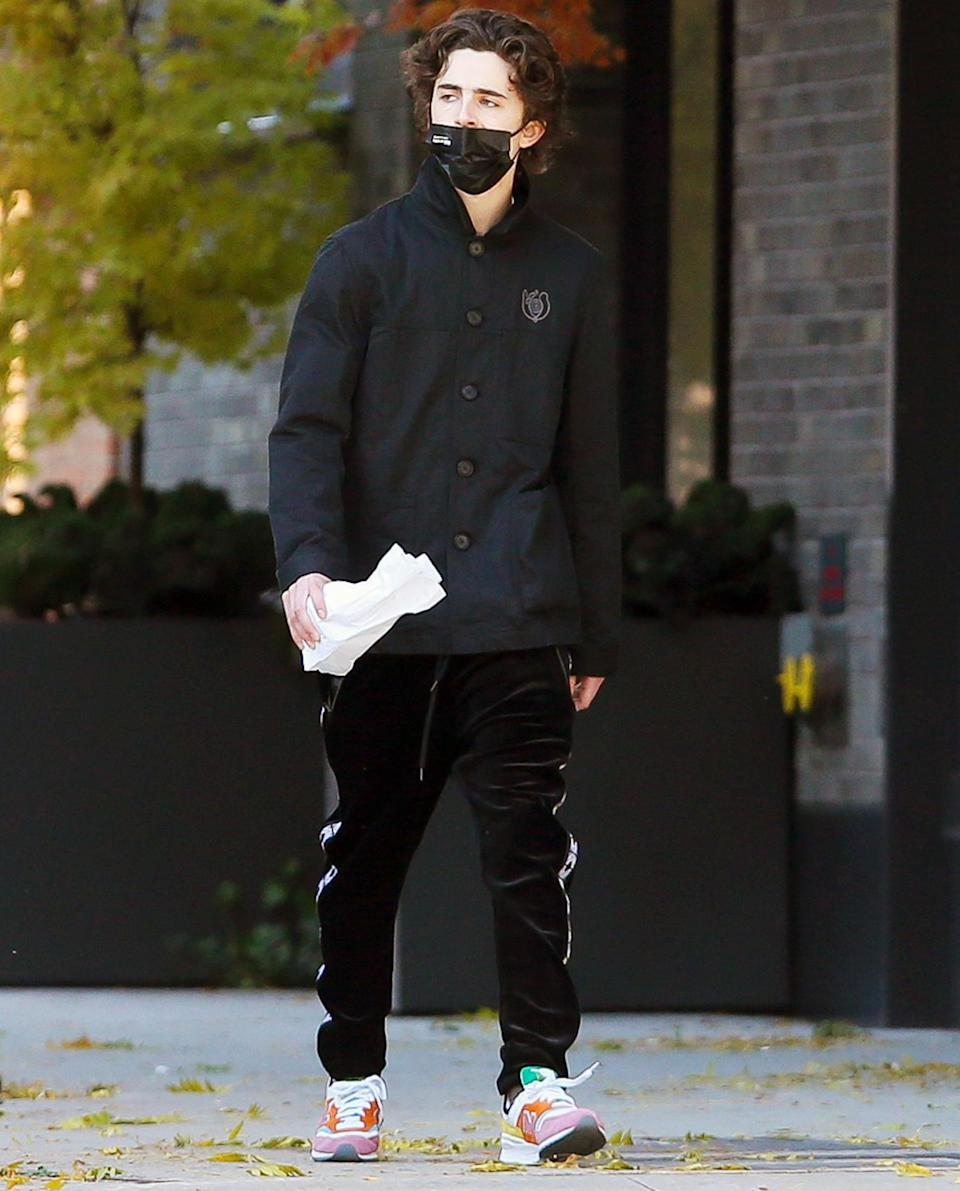 <p>Timothée Chalamet wears a black mask, jacket and sneakers on his walk through N.Y.C. on Thursday. </p>