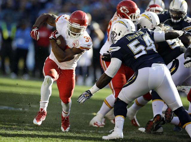 Kansas City Chiefs running back Knile Davis, left, gets past the San Diego Chargers defense during the first half of an NFL football game, Sunday, Dec. 29, 2013, in San Diego. (AP Photo/Lenny Ignelzi)