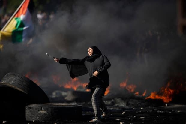 A Palestinian woman throws a rock toward Israeli forces at the Hawara checkpoint, south of the West Bank city of Nablus, Tuesday. Protests and clashes in the occupied territory have spread and so far claimed at least 12 lives.