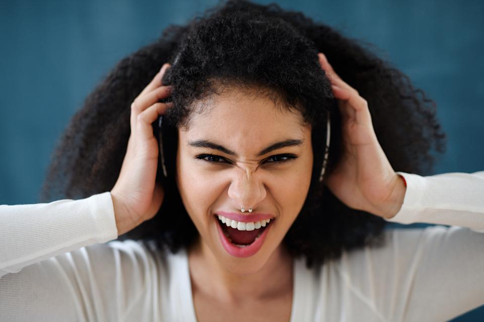 Close-up portrait of young woman with headphones indoors at home, listening to music.