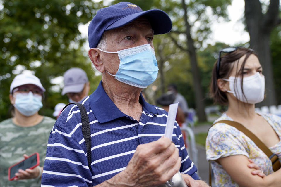 Tennis fans show their proof of vaccination cards for entry to attend the first round of the US Open tennis championships, Monday, Aug. 30, 2021, in New York. (AP Photo/John Minchillo)