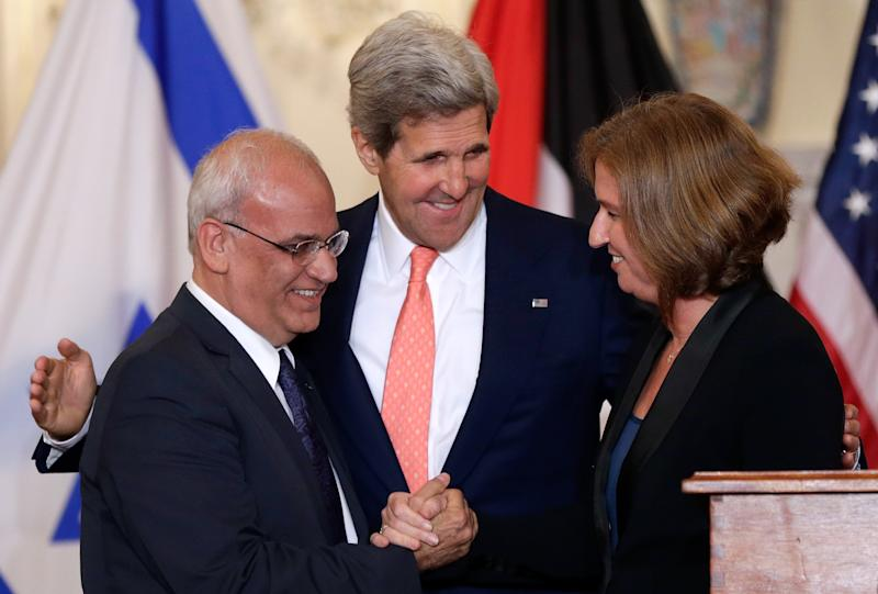 US Secretary of State John Kerry (centre) watches as Palestinian chief negotiator Saeb Erekat (left) shakes hands with Israeli Justice Minister Tzipi Livni during a press conference in Washington, on July 30, 2013