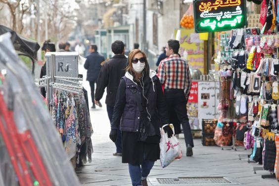 Woman wears protective mask while walking along the side of a street in the Iranian capital Tehran (AFP via Getty Images)