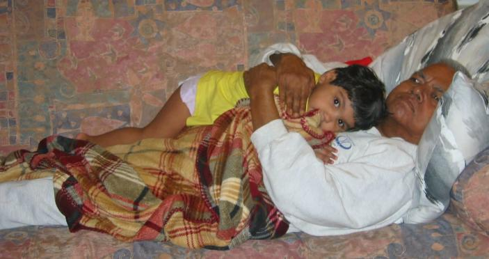 A young Meena Kumar snuggles with her grandfather. (Courtesy of Jayashree Subrahmonia)
