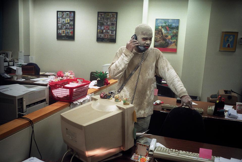 A man on the phone in an office, covered with dust.