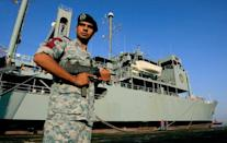 A member of Iran's special forces stands guard on the dock alongside the Kharg during a port call in Sudan in October 2012