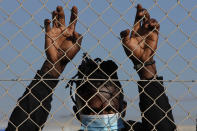 A migrant wearing a face mask stands behind a fence inside a refugee camp in Kokkinotrimithia outside of capital Nicosia, Cyprus, Friday, Feb. 5, 2021. Cyprus' Interior Minister Nicos Nouris said this week that the east Mediterranean island nation whose closest point to Syria is around 150 kilometers (93 miles), remains first among all other European Union member states with the most asylum applications relative to its population. Last year, the country of around 1.1 million people racked up 7,000 asylum applications - most of them from Syria. (AP Photo/Petros Karadjias)