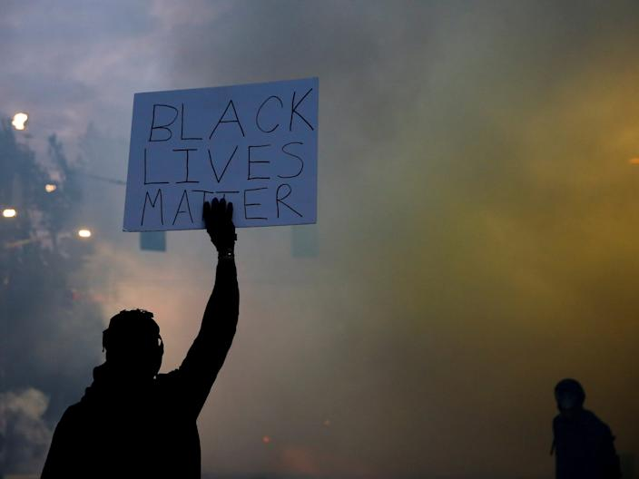 """A person holds a """"Black Lives Matter"""" sign at a protest in Seattle, Washington on June 1, 2020."""