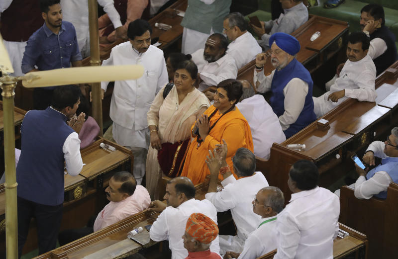 FILE- In this May 25, 2019 file photo, newly elected lawmaker Pragya Singh Thakur, center in orange dress, greets other lawmakers on her arrival at Bharatiya Janata Party parliamentary and their alliance meeting to elect Narendra Modi as their leader in New Delhi, India. Thakur, who won a seat from Bhopal in central India, is awaiting trial in connection with a 2008 explosion in Malegaon in western India that killed seven people. India's recent national election delivered a historic victory to Prime Minister Narendra Modi's Hindu nationalist party, but also exposed the influence of money, power and questionable morality on the world's largest democracy.(AP Photo/Manish Swarup, File)