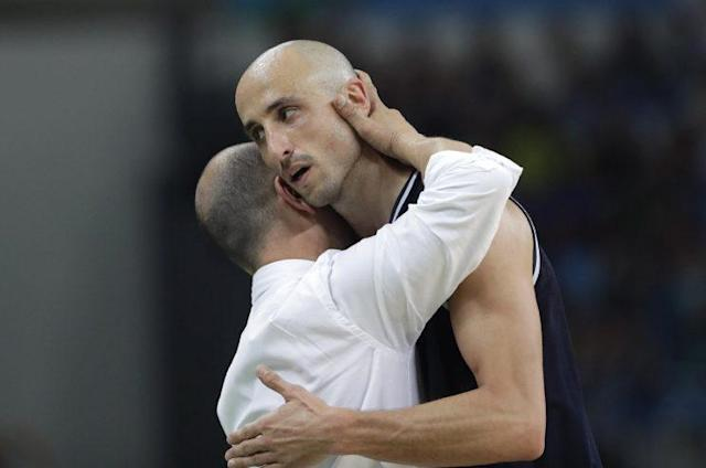 "Argentina head coach Sergio Santos Hernandez, left, hugs <a class=""link rapid-noclick-resp"" href=""/nba/players/3380/"" data-ylk=""slk:Manu Ginobili"">Manu Ginobili</a>, right, as he comes off the court during a quarterfinal game against the United States. (AP)"