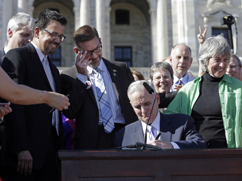 FILE – In this May 14, 2013, file photo Minnesota Gov. Mark Dayton signs the gay marriage bill in front of the State Capitol in St. Paul. Minnesota became the 12th state to legalize gay marriage. Three states and three countries have approved same-sex unions in just the two months since the Supreme Court heard arguments on the issue. Close observers on both sides of the divide are wondering whether such developments might affect the justices' consideration, particularly that of Justice Anthony Kennedy, which is likely to be decisive. Sponsors of the bill, Sen. Scott Dibble, second from left, and Rep. Karen Clark, right, both gay lawmakers, watch. (AP Photo/Jim Mone, File)