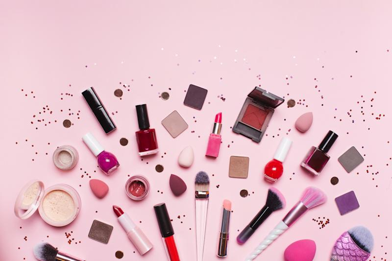 Top view of set of assorted tools and products for makeup application placed near shiny glitter on pink background
