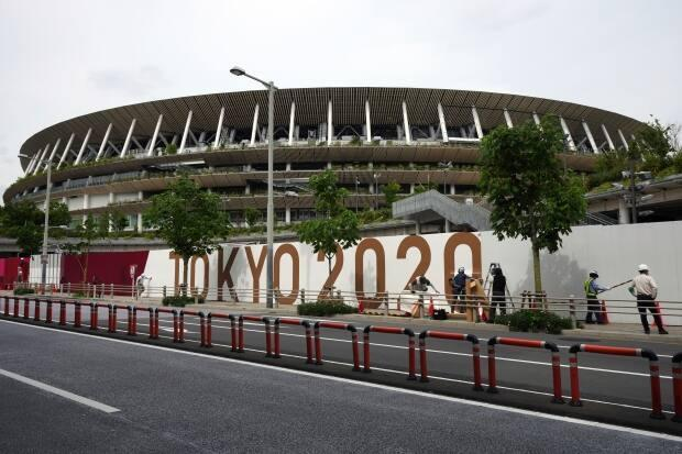 Workers paste the overlay on the wall of the National Stadium, where the opening ceremony and many other events are scheduled for the Tokyo Games. (Eugene Hoshiko/The Associated Press - image credit)