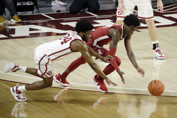 Oklahoma's Elijah Harkless (24) and Alabama's Keon Ellis (14) fight for the ball during the second half of an NCAA college basketball game in Norman, Okla., Saturday, Jan. 30, 2021. (AP Photo/Garett Fisbeck)