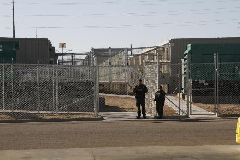 Border Patrol agents wait to reporters an immigration holding facility, Tuesday, Feb. 25, 2020, in El Paso, Texas. The complex of modular buildings can house and process 1,040 and will replace tents hastily erected for processing last spring.  (AP Photo/Cedar Attanasio)