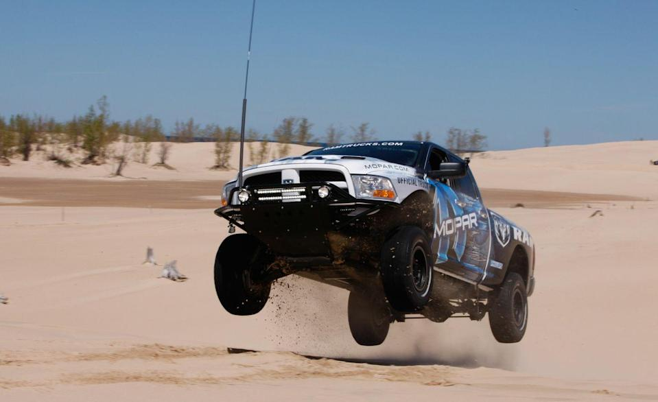 """<p>Ram has yet to offer a factory off-road truck with the same dune-running capability as Ford's F-150 Raptor, but since 2011 it has offered <a href=""""http://www.caranddriver.com/reviews/2011-mopar-ram-runner-road-test-review"""" rel=""""nofollow noopener"""" target=""""_blank"""" data-ylk=""""slk:the Ram Runner upgrade kit"""" class=""""link rapid-noclick-resp"""">the Ram Runner upgrade kit</a> for the 1500 pickup through its Mopar accessories catalog. The Ram Runner gear transforms a typical half-ton Ram pickup into a baby trophy truck and a convincing Raptor competitor, advancing wheel travel at all four corners to a useful 14 inches and adding a bunch of hard-core suspension components designed for one thing: sweet jumps. We couldn't resist.</p>"""