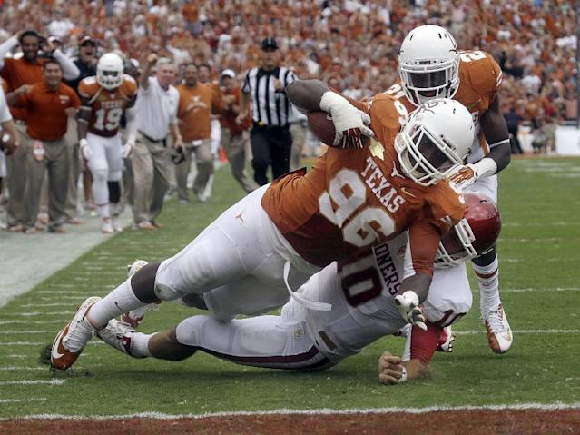 Texas defensive tackle Chris Whaley (96) scores a touchdown after intercepting a pass against Oklahoma quarterback Blake Bell (10) during the first half of an NCAA college football game at the Cotton Bowl Saturday, Oct. 12, 2013, in Dallas. Looking on is Texas cornerback Duke Thomas (21). (AP Photo/LM Otero)
