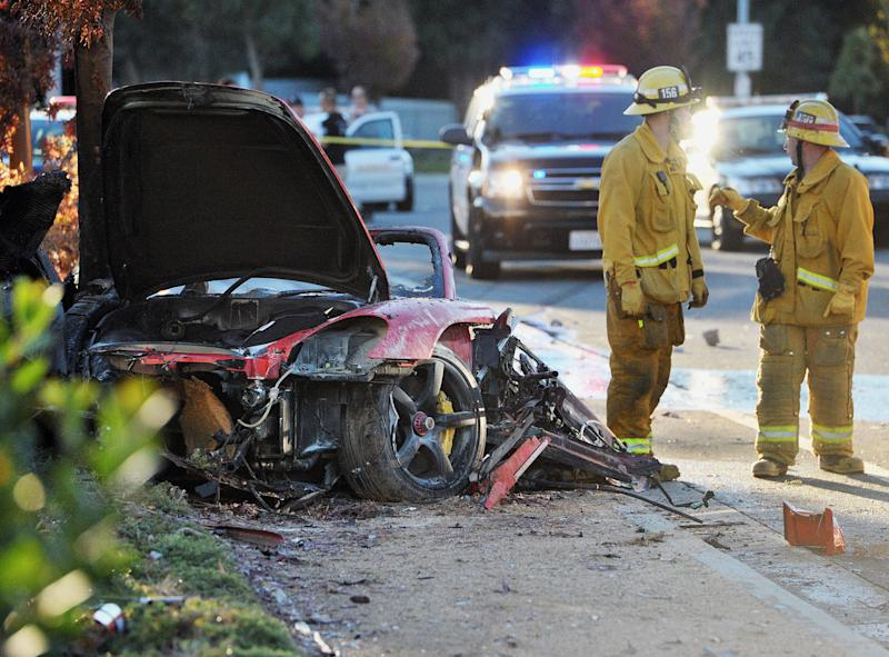 "Sheriff's deputies work near the wreckage of a Porsche that crashed into a light pole on Hercules Street near Kelly Johnson Parkway in Valencia, Calif., on Saturday, Nov. 30, 2013. A publicist for actor Paul Walker says the star of the ""Fast & Furious"" movie series died in the crash north of Los Angeles. He was 40. Ame Van Iden says Walker died Saturday afternoon. No further details were released. (AP Photo/The Santa Clarita Valley Signal, Dan Watson)"