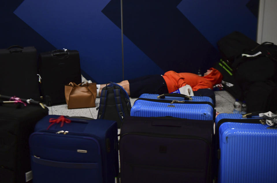 A passenger sleeps surrounded by suitcases at Gatwick airport, as the airport remains closed after drones were spotted over the airfield last night and this morning, in Gatwick, England, Thursday, Dec. 20, 2018. Drones spotted over the runway forced the shutdown of London's Gatwick Airport on Thursday during one of the busiest times of the year, stranding or delaying tens of thousands of Christmas-season travelers and setting off a hunt for the operator of the intruding aircraft. (Victoria Jones/PA via AP)