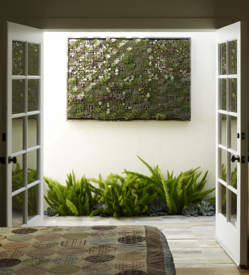 This undated publicity photo courtesy of Flora Grubb Gardens shows a large living succulent picture hanging outside a bedroom in San Francisco. Living pictures, cuttings of assorted succulents woven together in everything from picture frames to pallet boxes, are hot among garden designers and landscapers this spring as an easy, modern way to add color and texture to an outdoor space.  (AP Photo/Flora Grubb Gardens, Marion Brenner)