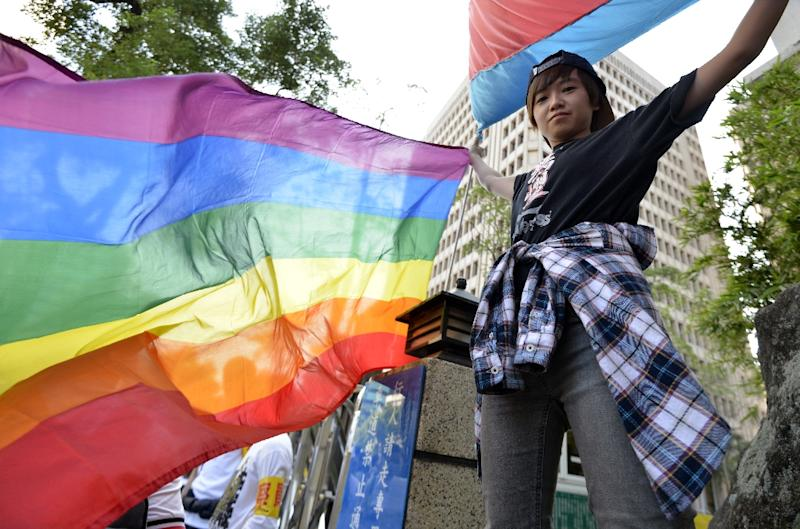 A supporter of same-sec marriage holds a rainbow flag outside the Parliament in Taipei on November 17, 2016