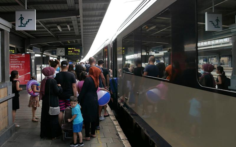 Belgians board a busy train to the beach - as the virus rate soars - Sylvain Plazy/AP