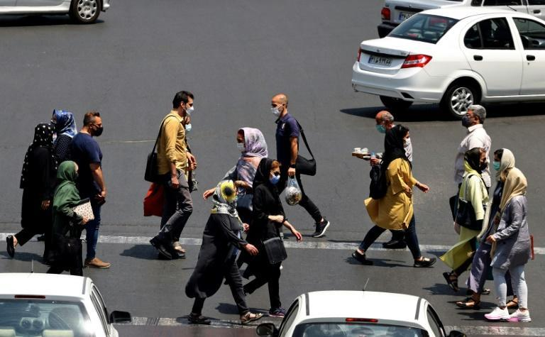 Iranians, mask-clad due to the coronavirus pandemic, cross a street in the capital Tehran, on July 3, 2021