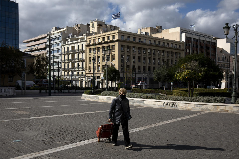 A woman, wearing a protective mask against the spread of coronavirus, walks at a central square, in Athens, Saturday, Nov. 21, 2020. The government imposed a second lockdown nationwide on Nov. 7, expanding regional restrictions, following a dramatic surge in COVID-19 cases. (AP Photo/Yorgos Karahalis)