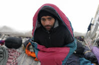A migrant is covered in a sleeping bag in a temporary shelter at the Lipa camp northwestern Bosnia, near the border with Croatia, Saturday, Dec. 26, 2020. Hundreds of migrants are stranded in a burnt-out squalid camp in Bosnia as heavy snow fell in the country and temperatures dropped during a winter spell of bad weather after fire earlier this week destroyed much of the camp near the town of Bihac that already was harshly criticized by international officials and aid groups as inadequate for housing refugees and migrants.(AP Photo/Kemal Softic)