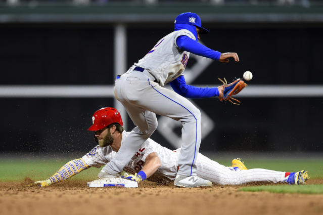 Philadelphia Phillies' Bryce Harper, bottom, slides into second base safely past New York Mets' Amed Rosario after Harper hit an RBI single off Noah Syndergaard during the third inning of a baseball game, Monday, April 15, 2019, in Philadelphia. (AP Photo/Derik Hamilton)
