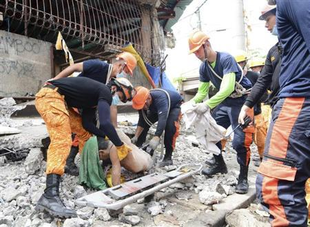 ATTENTION EDITORS - VISUAL COVERAGE OF SCENES OF INJURY OR DEATH Rescuers retrieve a body from the debris at a fishing port that was damaged after a earthquake struck Cebu city, central Philippines October 15, 2013. REUTERS/STRINGER
