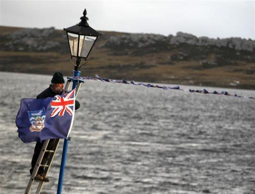 A man hangs a Falklands flag in Stanley June 14, 2012, during commemorations for the 30th anniversary of the Falklands War. The tiny Falkland Islands will ask 3,000 inhabitants whether they want to stay part of Britain's self-governing overseas territories in a referendum designed to outflank Argentina's sovereignty claims to the South Atlantic archipelago.